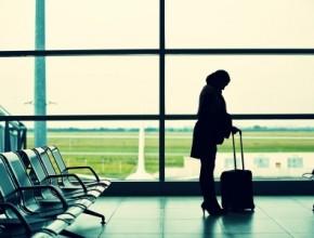 Kvinna med resväska i vänthallen på en flygplats